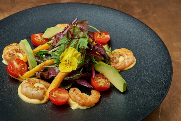 Salad with fried shrimp, arugula, cherry tomatoes, avocado and mango in a black ceramic plate