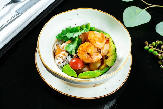 Salad with fried shrimp, rice, avocado, green beans and cherry tomatoes in a yellow bowl on a dark background. seafood. healthy and wholesome food. buddha bowl