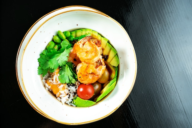 Salad with fried shrimp, rice, avocado, green beans and cherry tomatoes in a yellow bowl on a dark background.