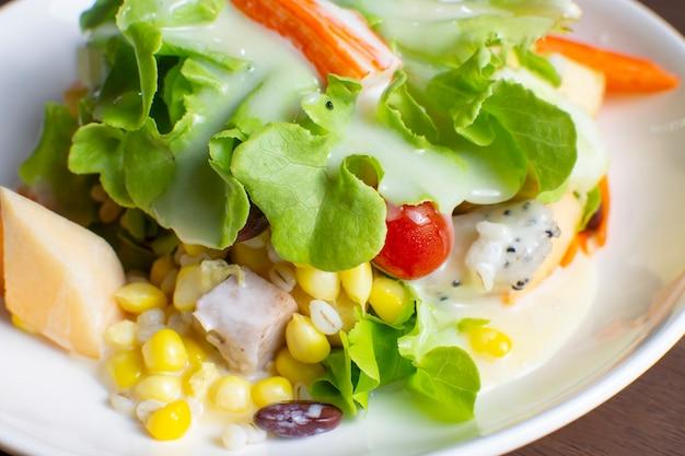 Салат из фруктов и свежих овощей с заправкой для салата в белом блюде на деревянном столе