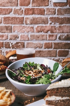 Salad with goat cheese, homemade hamburgers with french fries, drink and cake on the wooden table. isolated vertical image.
