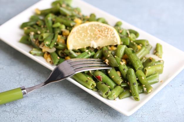 Салат с зеленой фасолью и кукурузой, кунжутом на тарелке, на цветном деревянном столе