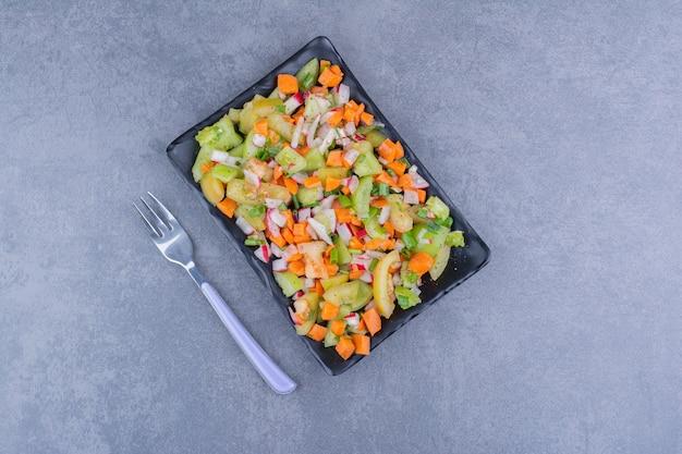 세라믹 접시에 녹색 야채와 방울토마토를 곁들인 샐러드