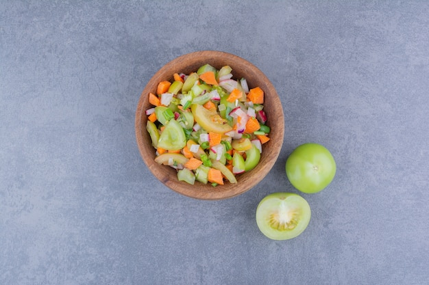 나무 접시에 녹색 야채와 방울 토마토를 곁들인 샐러드