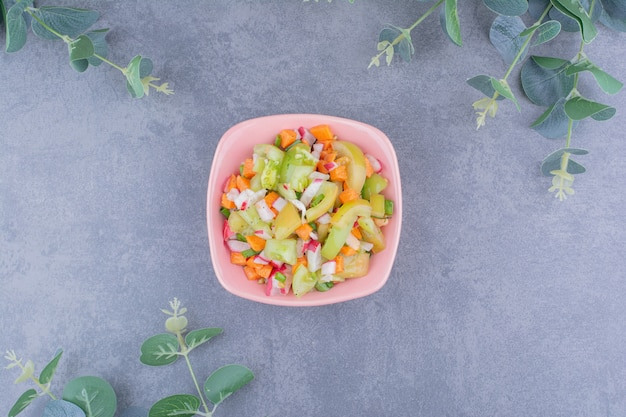 Salad with green vegetable and cherry tomatoes in ceramic dishes