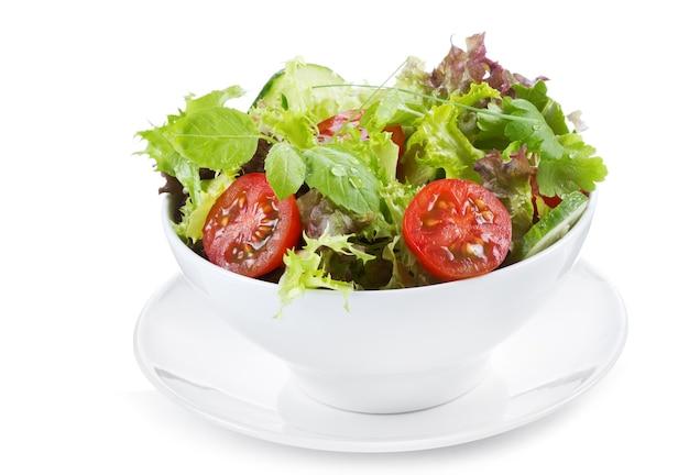 Салат с зеленью и овощами на белом фоне