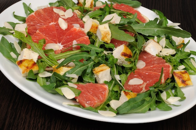 Salad with grilled chicken and arugula, grapefruit, almonds