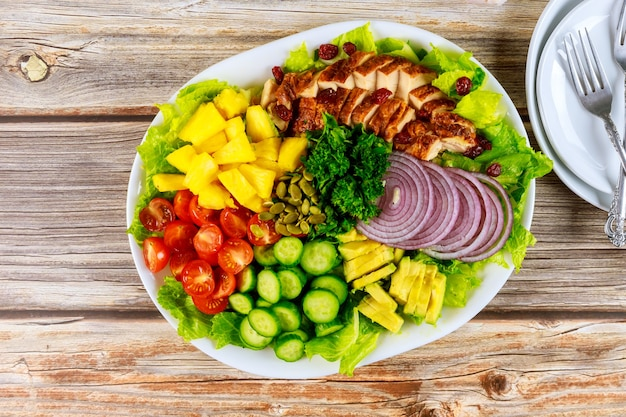 鶏胸肉のグリルとロメインレタス、アボカド、パイナップル、きゅうりのサラダ。
