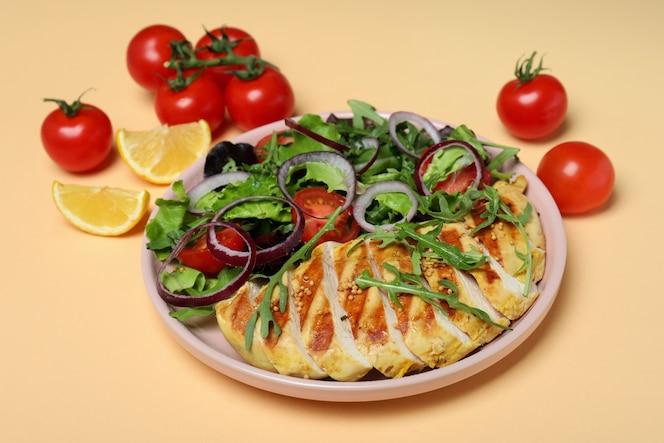 insalata con pollo alla griglia e ingredienti sul beige