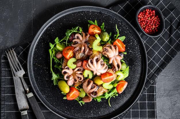 タコのグリル、ポテト、ルッコラ、トマト、オリーブのサラダ。黒の背景。上面図