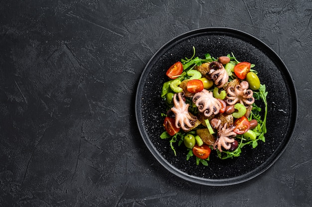 Salad with grilled octopus, potatoes, arugula, tomatoes and olives. black background. top view. copyspace