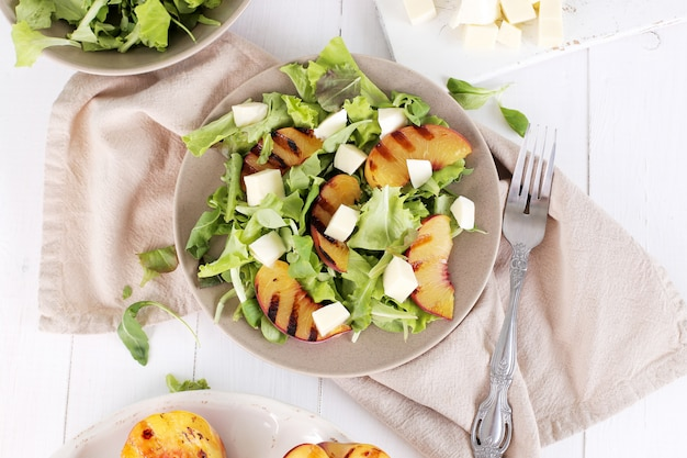 Salad with grilled peaches, arugula and mozzarella cheese