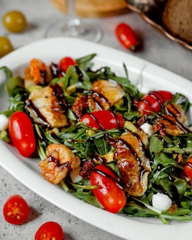 Salad with grilled shrimps and tomatoes on table