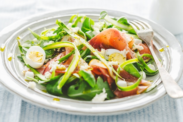 Salad with ham, asparagus, eggs and cheese served on plate.