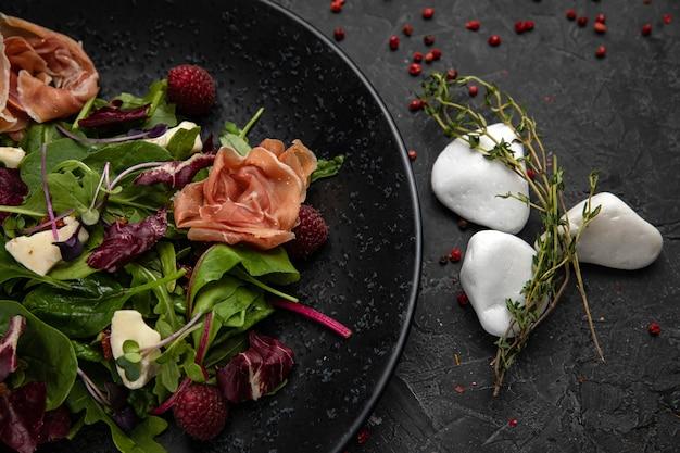 Салат с ветчиной, зеленью, малиной, микрозеленью на темном бетонном столе