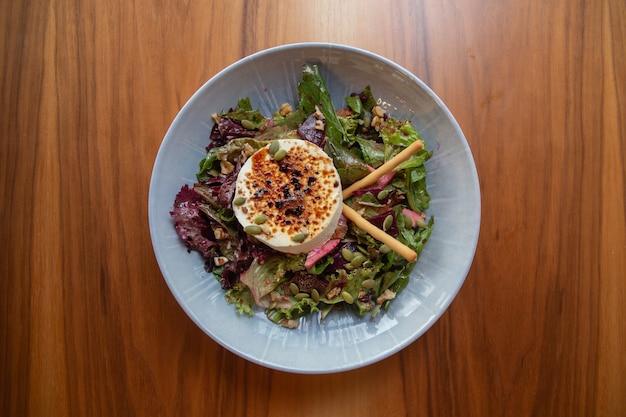 Салат с зеленью, сыром и семенами. здоровая пища.