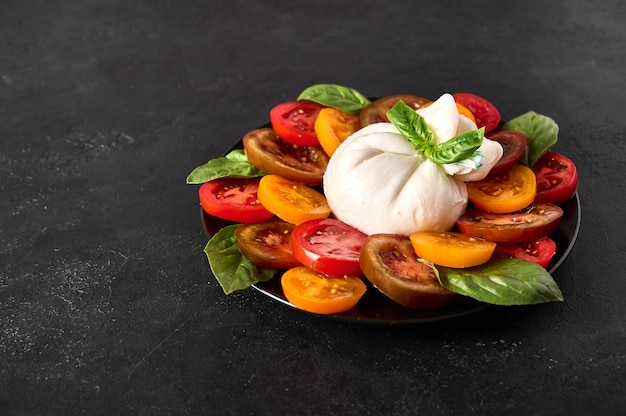 Салат с итальянским сыром буррата с базиликом и помидорами на темном текстурированном фоне крупным планом