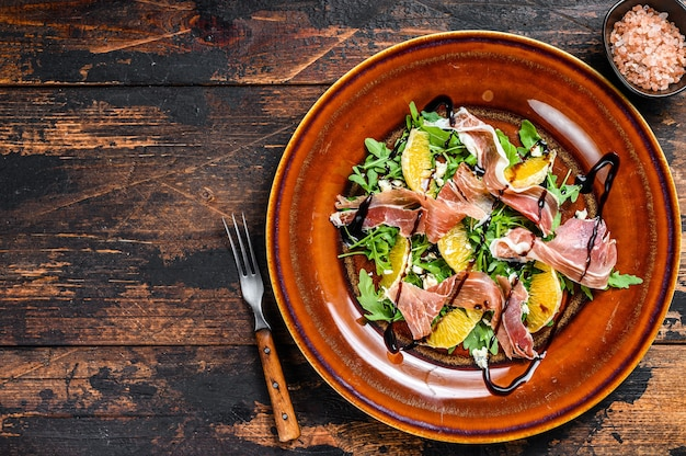Salad with jamon ham, parmesan cheese, arugula and tangerine on a plate. dark wooden table. top view. copy space.