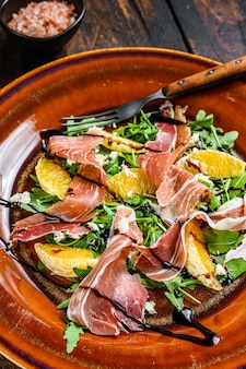 Salad with jamon ham, parmesan cheese, arugula and tangerine on a plate. dark wooden table. top view.