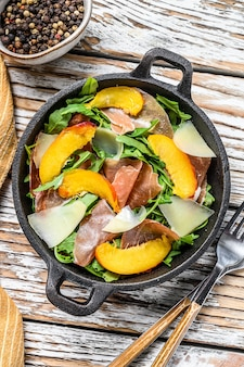 Salad with jamon iberico, arugula, peach and parmesan in a iron pan
