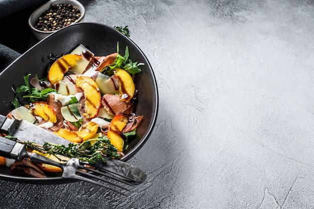 Salad with jamon iberico, arugula, peach and parmesan