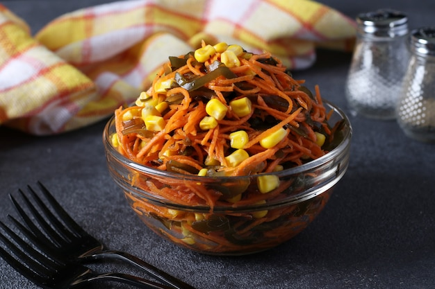 어두운 회색 배경에 투명한 그릇에 다시마, 당근, 옥수수를 넣은 샐러드. 건강한 식생활. 확대
