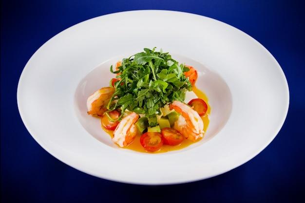 왕새우, 아루 굴라, 토마토, 아보카도가 들어간 샐러드. 파란색 배경에 흰색 접시에 평면 위치 최고보기.