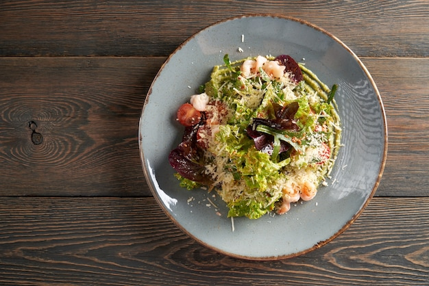 Салат с листьями салата и морепродуктами на пюре из авокадо