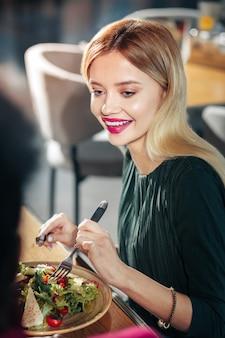 Салат с листьями салата красивая светловолосая женщина ест салат с листьями салата и помидорами