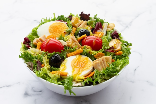 Салат с салатом, яйцом, тунцом, оливками и медово-горчичным винегретом на белом фоне
