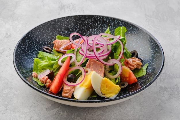Салат с листьями салата, лососем, помидорами, вареным яйцом и луком с оливками.
