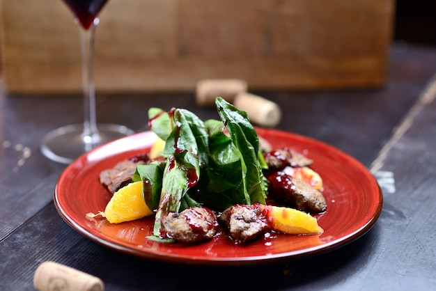 Salad with liver, spinach and orange on a red plate, on a wooden table