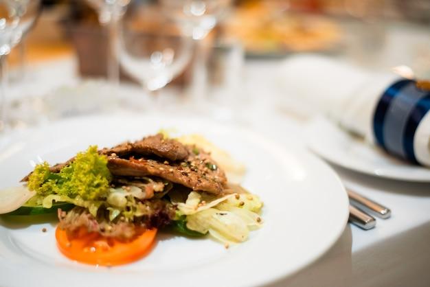 Салат с мясом и зеленью нарезанный мясной стейк с зеленым салатом на белой тарелке со столовыми приборами