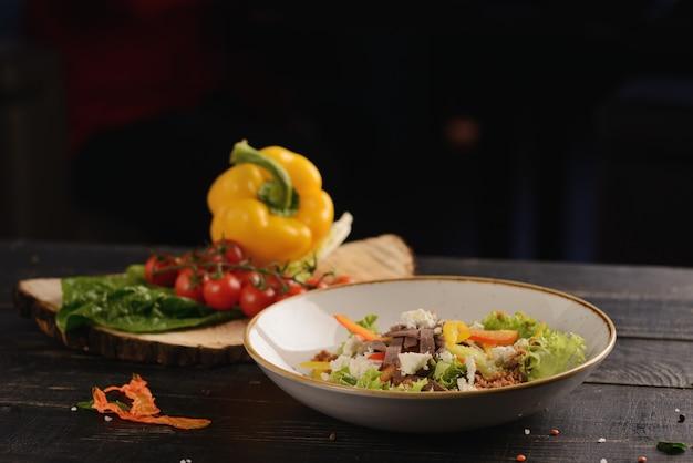 肉、ピーマン、レタス、クリームチーズのサラダ。木製テーブルの上の白い皿に。野菜の装飾付き