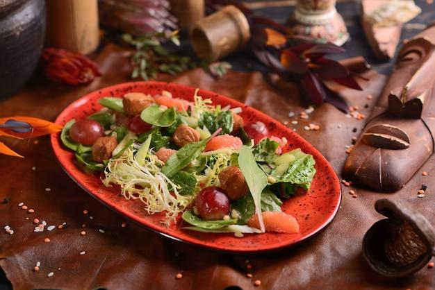 肉、ブドウ、オレンジのサラダ。赤いお皿に。アフリカの装飾