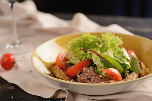 Salad with meat, tomatoes, sesame seeds and lettuce. in a yellow plate on a wooden table