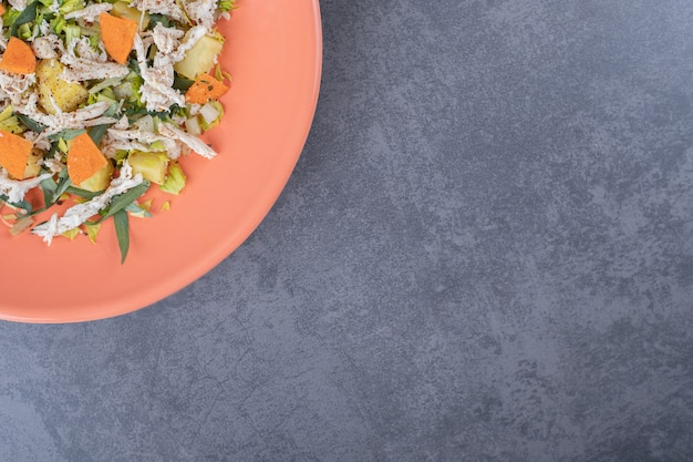 Insalata con pollo tritato su piastra arancione.