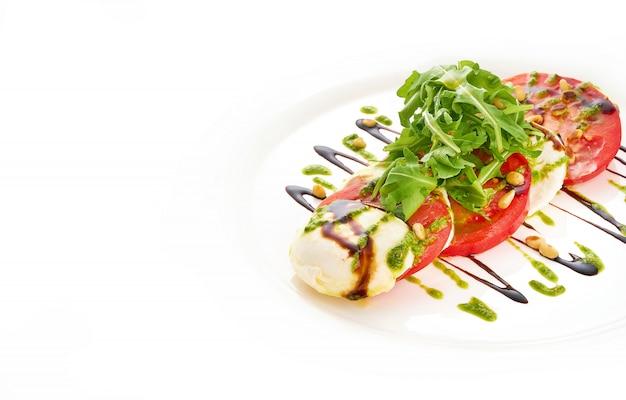 Салат с сыром моцарелла, помидорами, рукколой и соусом песто в белой тарелке.