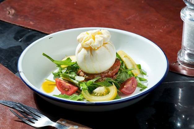 흰색 접시에 모짜렐라 burrata, arugula, 페스토, 체리 토마토 샐러드. 어두운 표면. 강한 빛
