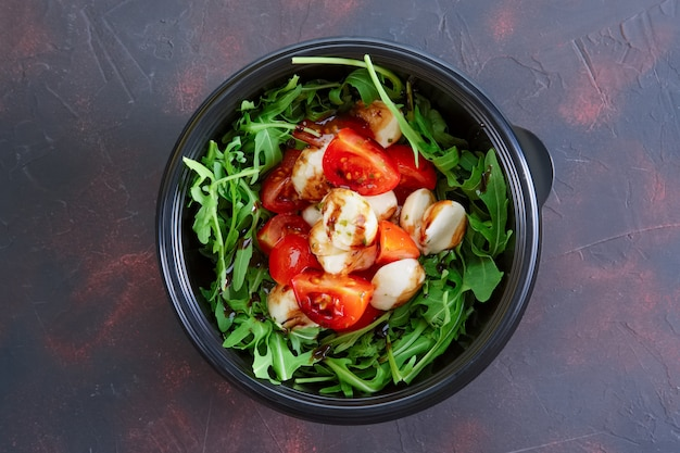 Salad with mozzarella, tomato and arugula in take away packaging