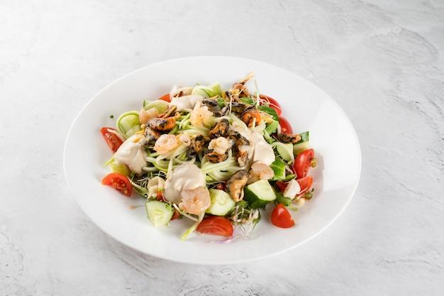 가벼운 탁자에 있는 하얀 접시에 홍합, 새우, 토마토 체리, 오이, 호박 파스타, 마이크로그린, 요구르트 소스를 곁들인 샐러드.
