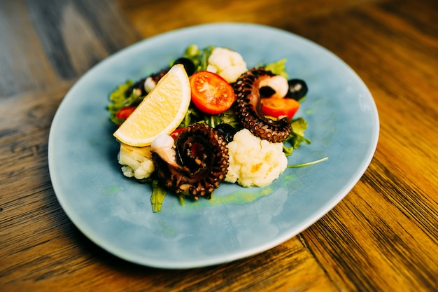 Salad with octopus and cauliflower on the plate.