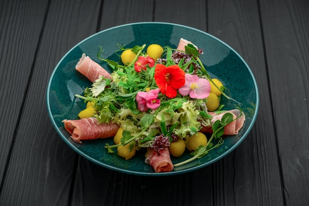 Salad with parma ham, jamon, tomatoes and arugula, black surface