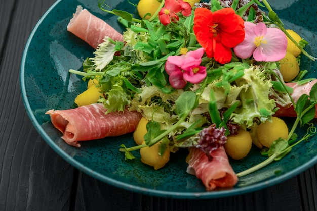 Salad with parma ham, jamon, tomatoes and arugula