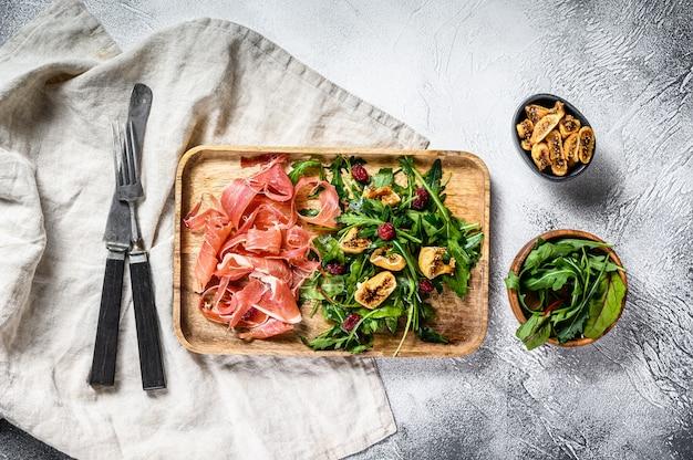 Салат с пармой, ветчиной прошутто, рукколой и инжиром. итальянские закуски. серая поверхность, вид сверху.
