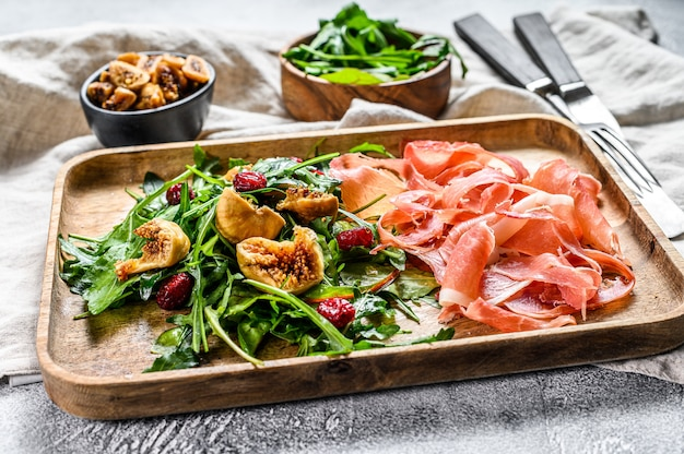 Salad with parma, prosciutto ham, arugula and figs. italian antipasti. gray background, top view.