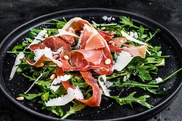 Salad with parma, prosciutto ham, arugula and parmesan. black background, top view.