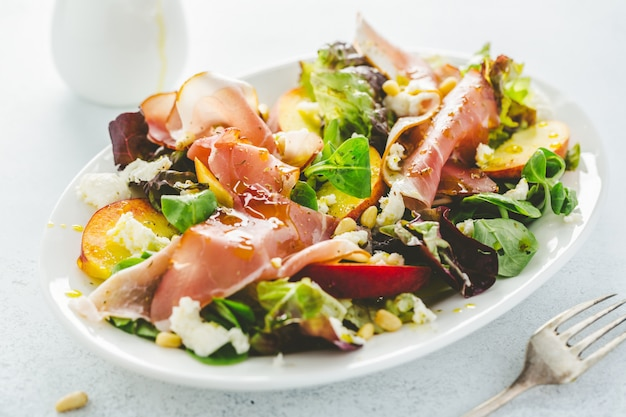 Salad with peaches, ham and cheese served on plate.