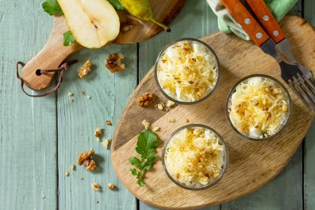 소박한 나무 탁자 위에 있는 배 햄 계란 호두 과일과 아루굴라 샐러드