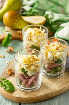 소박한 나무 테이블에 배 햄 계란 호두 과일과 아루굴라 샐러드